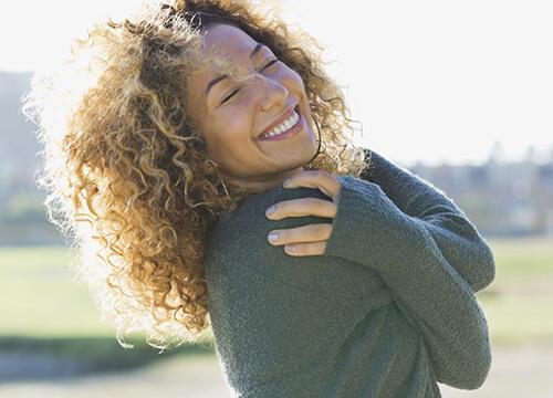 vrouw omhelst zichzelf vol zelfliefde